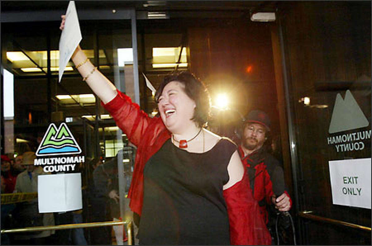 Mary Li emerges from the Multnomah County Building with the first marriage license issued to a gay couple.