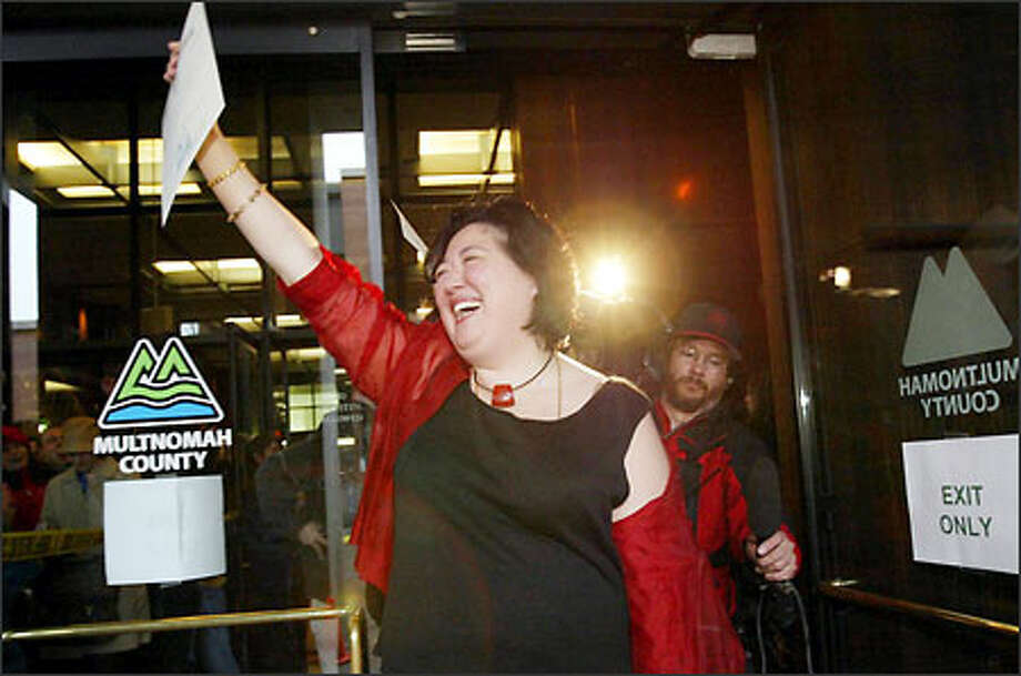 Mary Li emerges from the Multnomah County Building with the first marriage license issued to a gay couple. Photo: Joshua Trujillo, Seattlepi.com / seattlepi.com