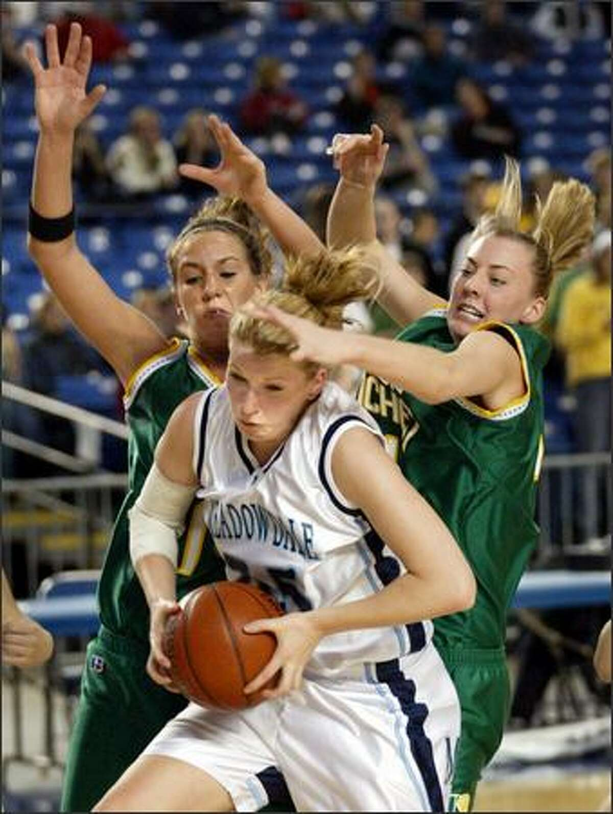 Bishop Blanchet players Krista Lersch (left) and Erika Pettersen trap Meadowdale senior Quinn Brewe, who had nine points and eight rebounds.