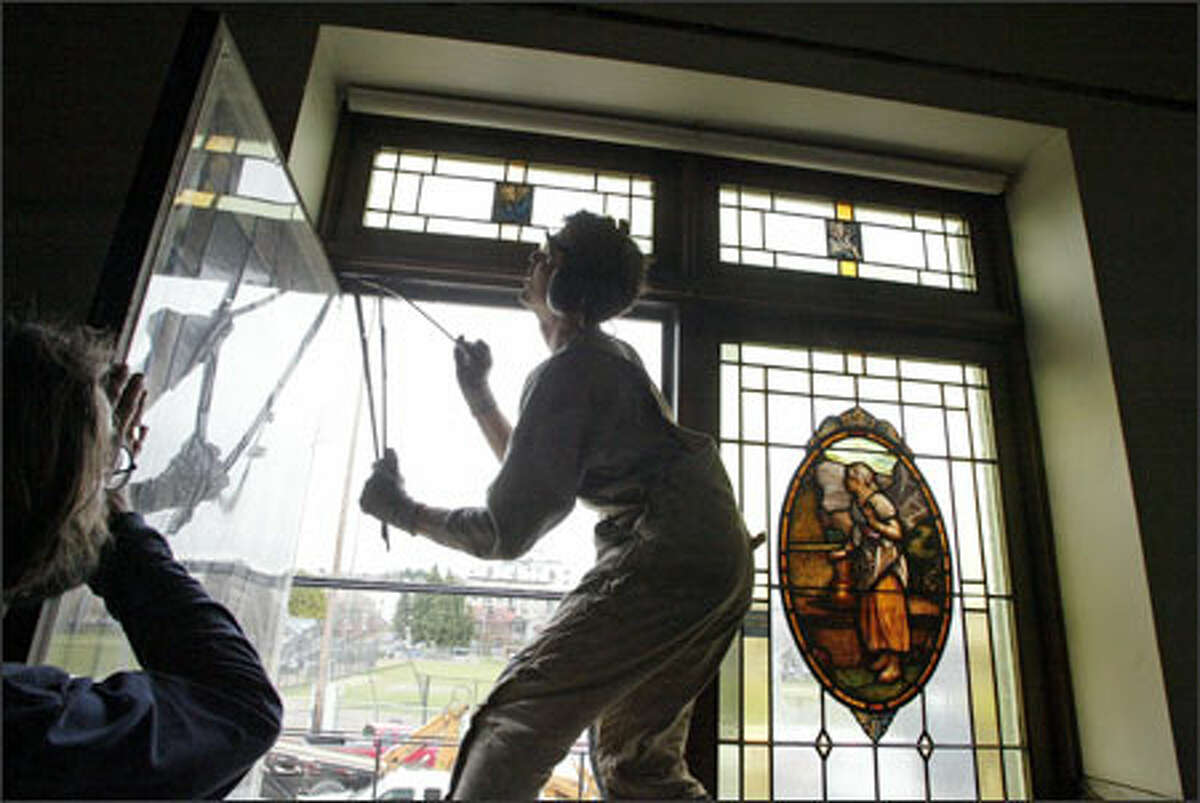 David Spangler, center, assisted by Jeff Masson, both of The Re Store, removes stained glass from the Seattle First Christian Church on Broadway, which is scheduled to be demolished in April. The Re Store has teamed up with Earthwise to salvage materials from the church, which sustained more than $1.5 million in damage after the Nisqually Quake hit in 2001.