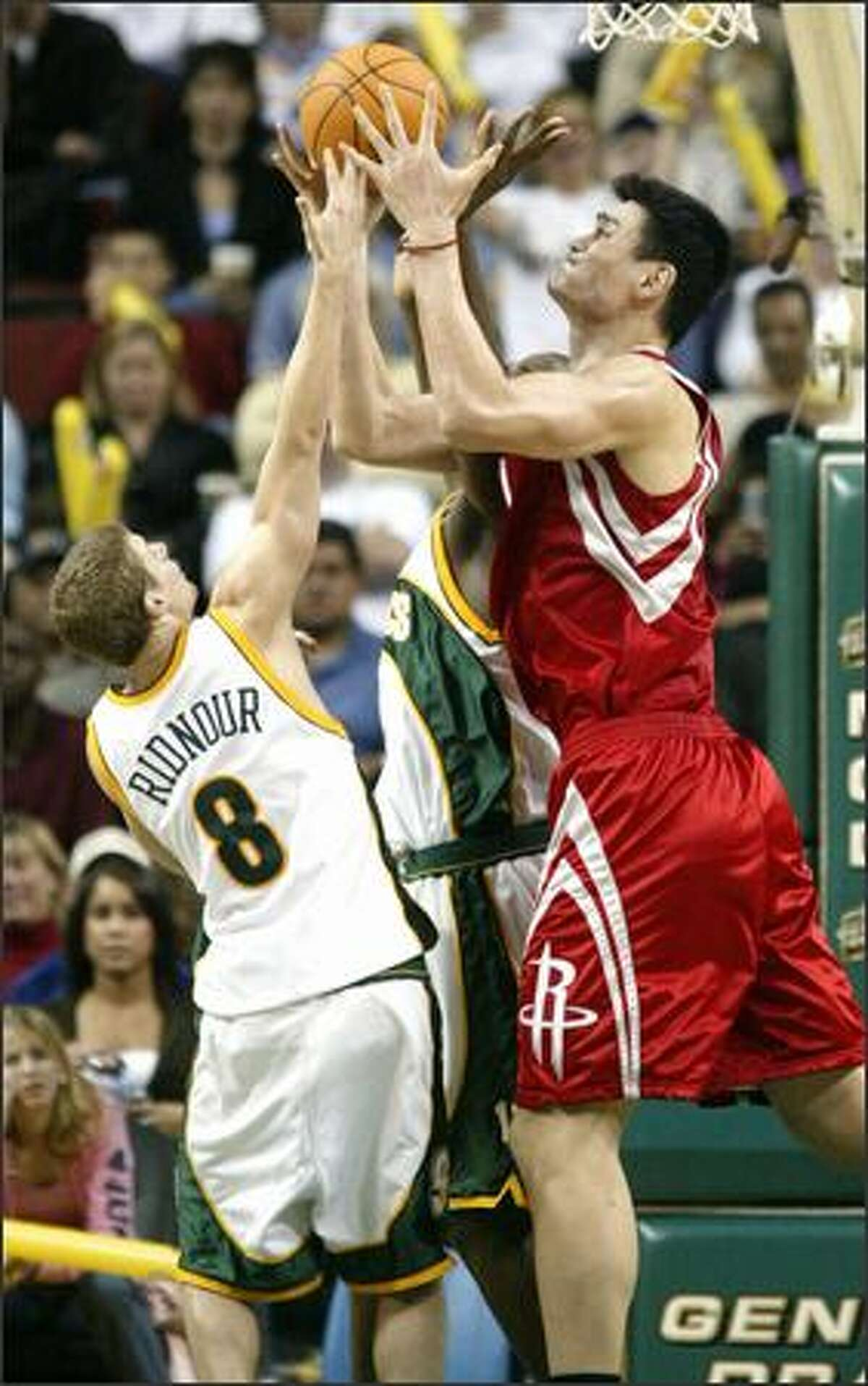 Enjoying a 16-inch height advantage, 7-foot-6 Yao Ming grabs a rebound from a straining Luke Ridnour. The Houston Rockets beat the Sonics 97-95.