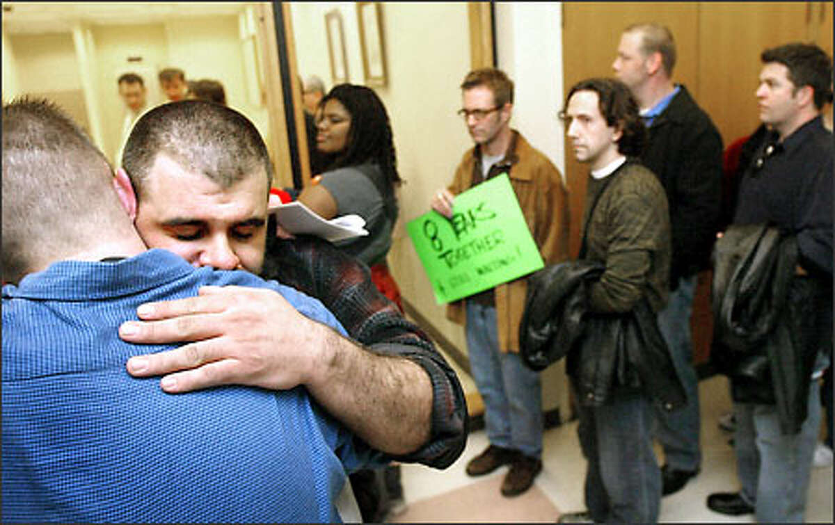 As other gay and lesbian couples wait in line to try to get marriage licenses, Seattle couple Will Jerome, facing camera, and John Kirby embrace after being denied a license at the King County Adminstration Building in Seattle yesterday. Later, protesters marched to demand the legal right to wed.