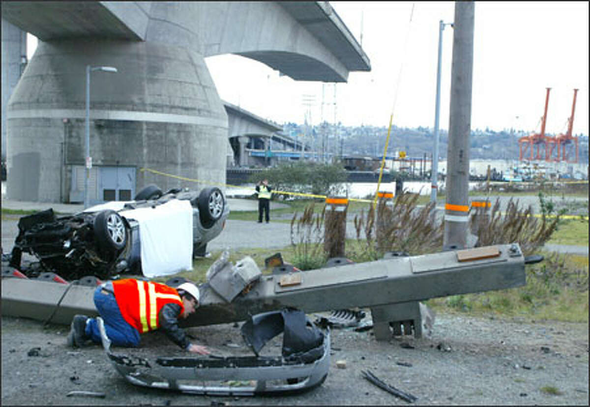 An investigator examines a guardrail after the car in back smashed through barriers and plunged off the Spokane Street Bridge in Seattle.