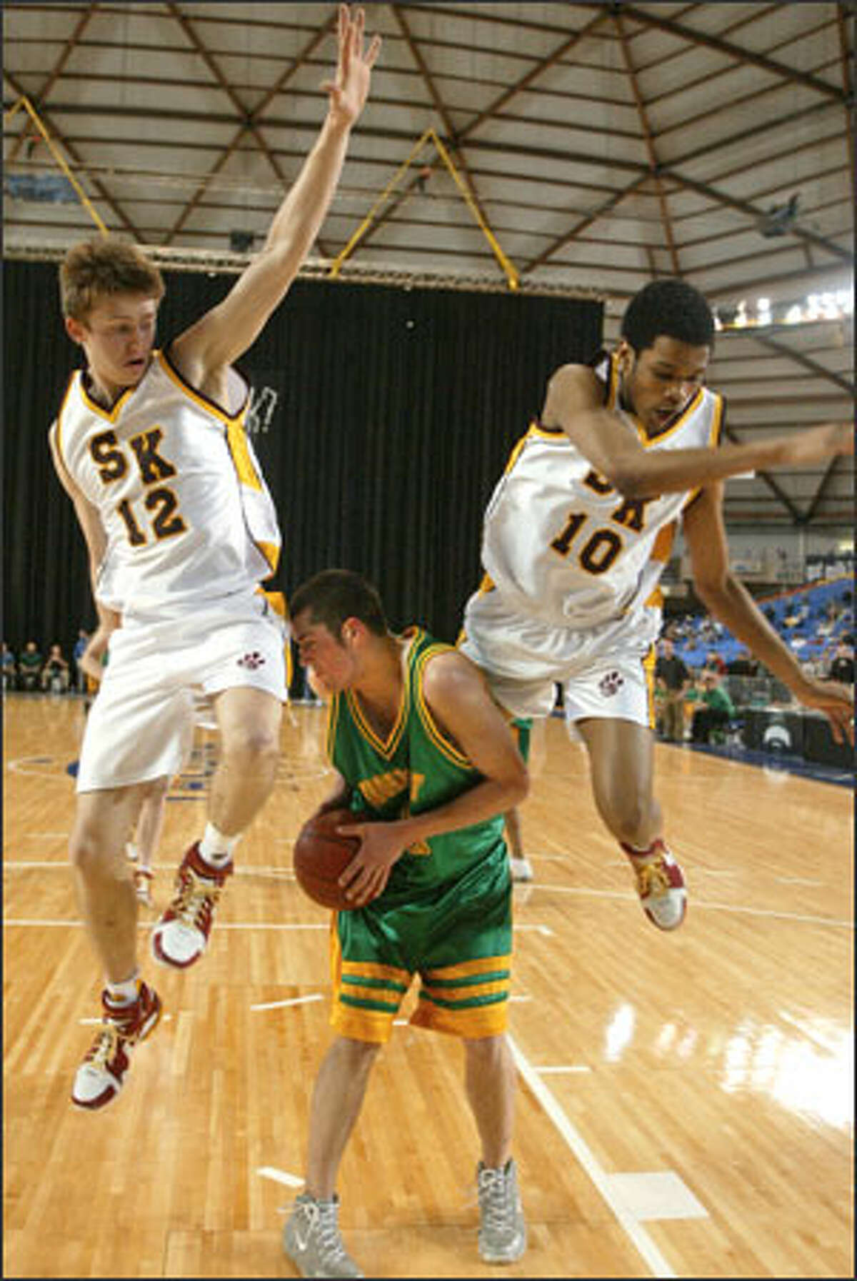 Roosevelt's David Grant ducks between high-flying South Kitsap defenders Conner Gehring and L.P. Neloms during the state high school basketball championships.