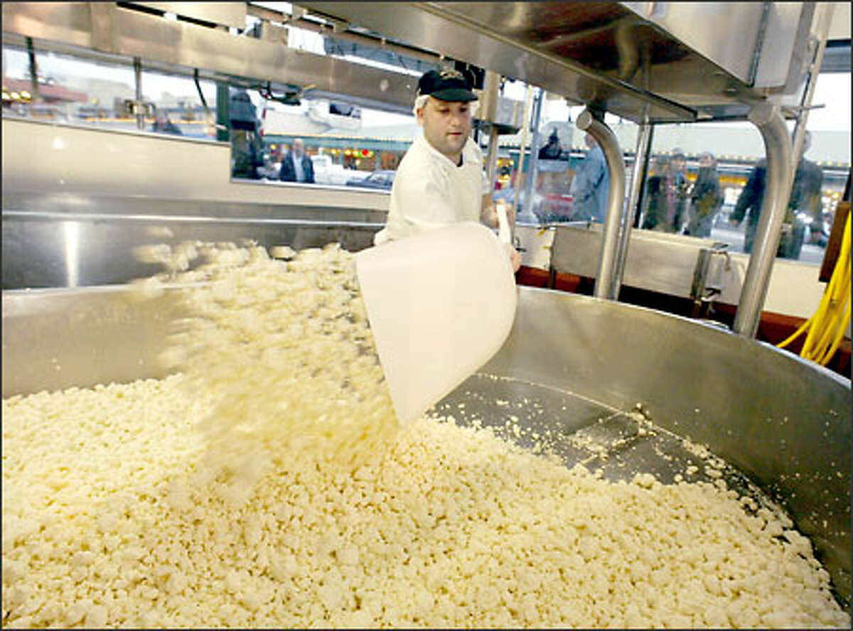 Cheesemaker Amir Rosenblatt turns the curds before putting them in a hoop to age for 45 days. Beecher's specializes in Jack cheese and a semihard cow's milk cheese.