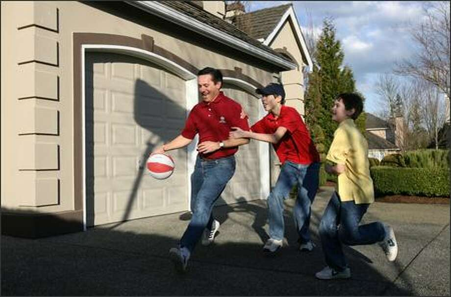 Dino Rossi is fouled by his son, Jake, 13, while his other son, Joseph, 10, runs to get in on the action as they shoot hoops in the driveway of their Sammamish home. Photo: Mike Urban, Seattle Post-Intelligencer / Seattle Post-Intelligencer
