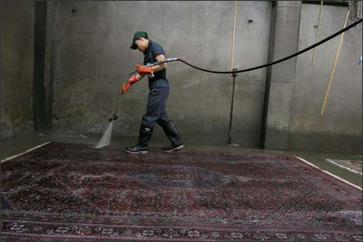 Employee Ket Hormthoum washes a rug at Emmanuel's Rug & Upholstery Cleaners in Seattle. The company has been in business since 1907.