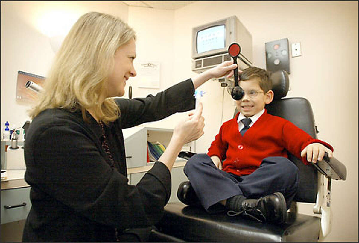 Isaiah Williams, 6, has his eyes examined by Karen Preston, a Redmond optometrist. She is checking his eyes for misalignment.