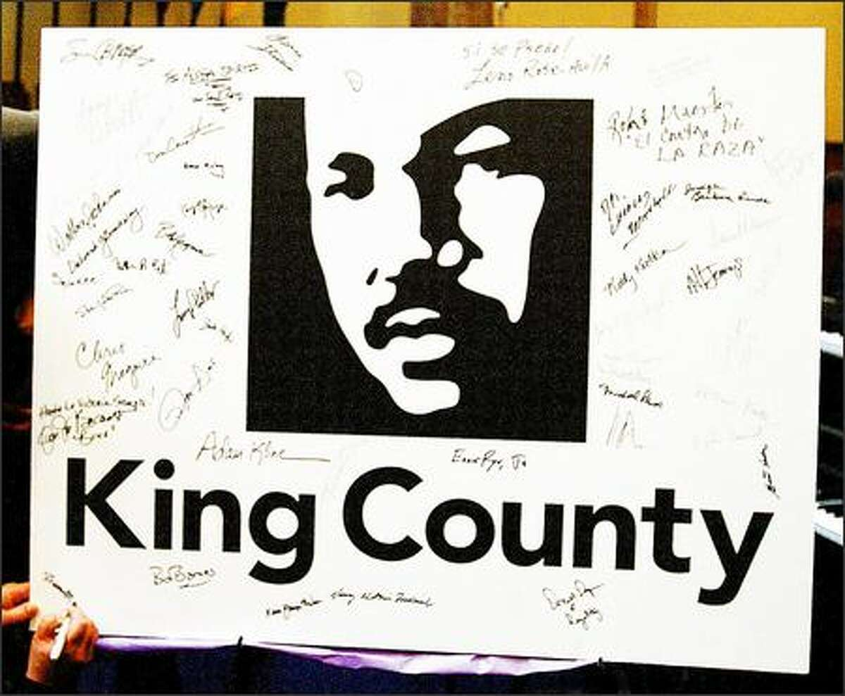 Sharon Maeda signs her name onto the lower left corner of a poster of the King County new logo of the image of Martin Luther King, Jr., which was unveiled Sunday afternoon at Mount Zion Baptist Church.