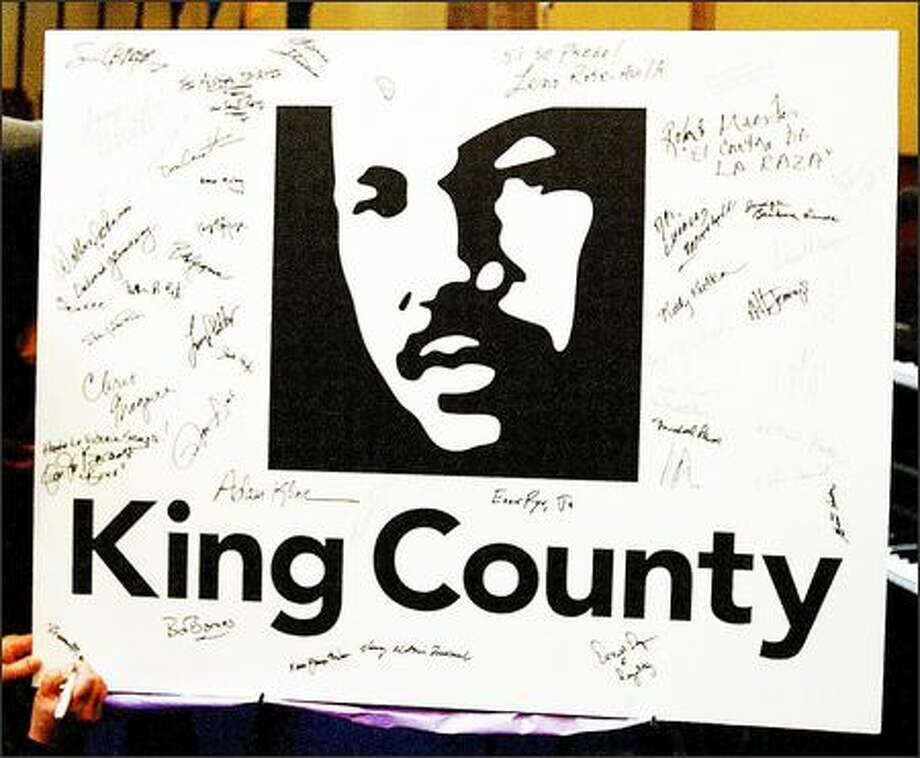 Sharon Maeda signs her name onto the lower left corner of a poster of the King County new logo of the image of Martin Luther King, Jr., which was unveiled Sunday afternoon at Mount Zion Baptist Church. Photo: Grant M. Haller, Seattle Post-Intelligencer / Seattle Post-Intelligencer
