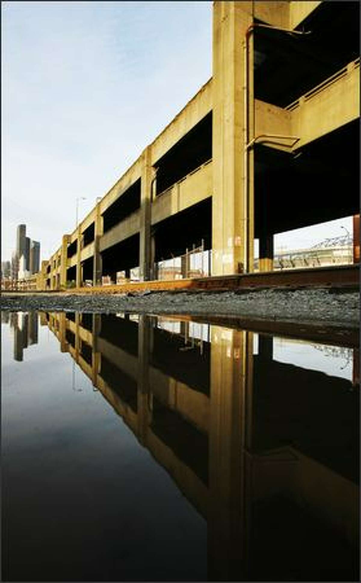 State Route 99, reflected in a waterfront mud puddle, rises to become the Seattle Viaduct near Atlantic Street.