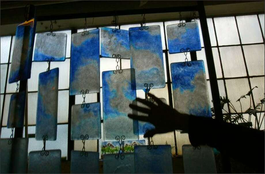 "Bedrock Industries sells glass curtains in its factory outlet in Seattle. Bedrock recycles glass from consumer and industrial waste and sells it as tiles, tumbled glass for decorative products,and finished garden art and gifts. ""We specialize in trash beautification."" said founder Maria Ruano. Photo: Karen Ducey, Seattle Post-Intelligencer / Seattle Post-Intelligencer"