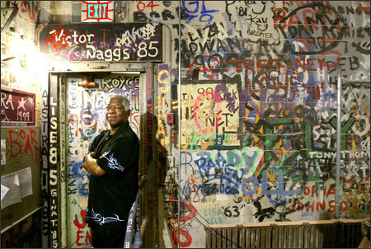 """1965 grad Robert Stephens stands by the """"drama wall"""" behind Garfield High School's auditorium that has carried the signatures of theater students for decades."""