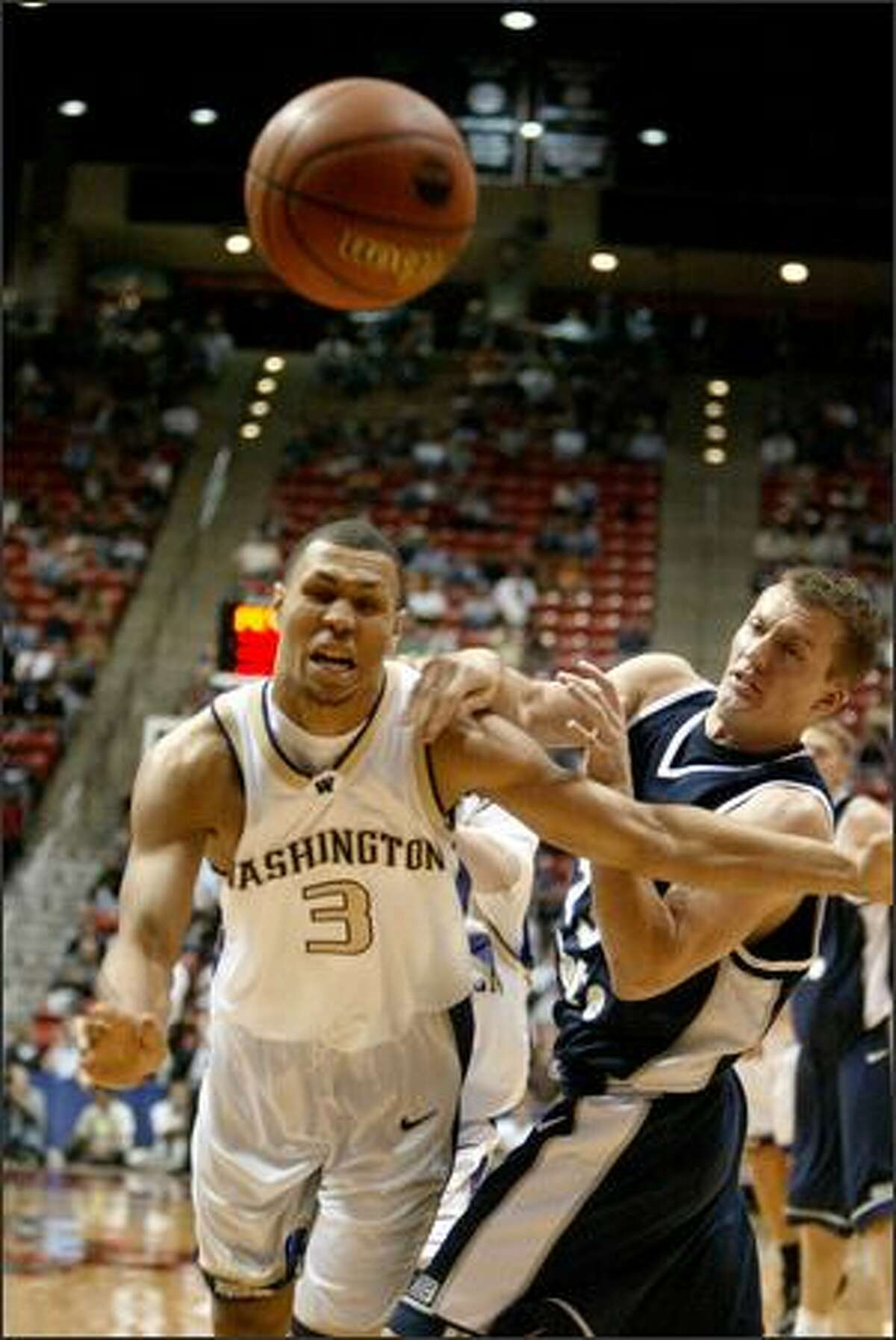Utah State's Chris Huber grabs a piece of Washington's Brandon Roy, left, as the two schools faced off in the NCAA Tournament. Washington won 75-61.