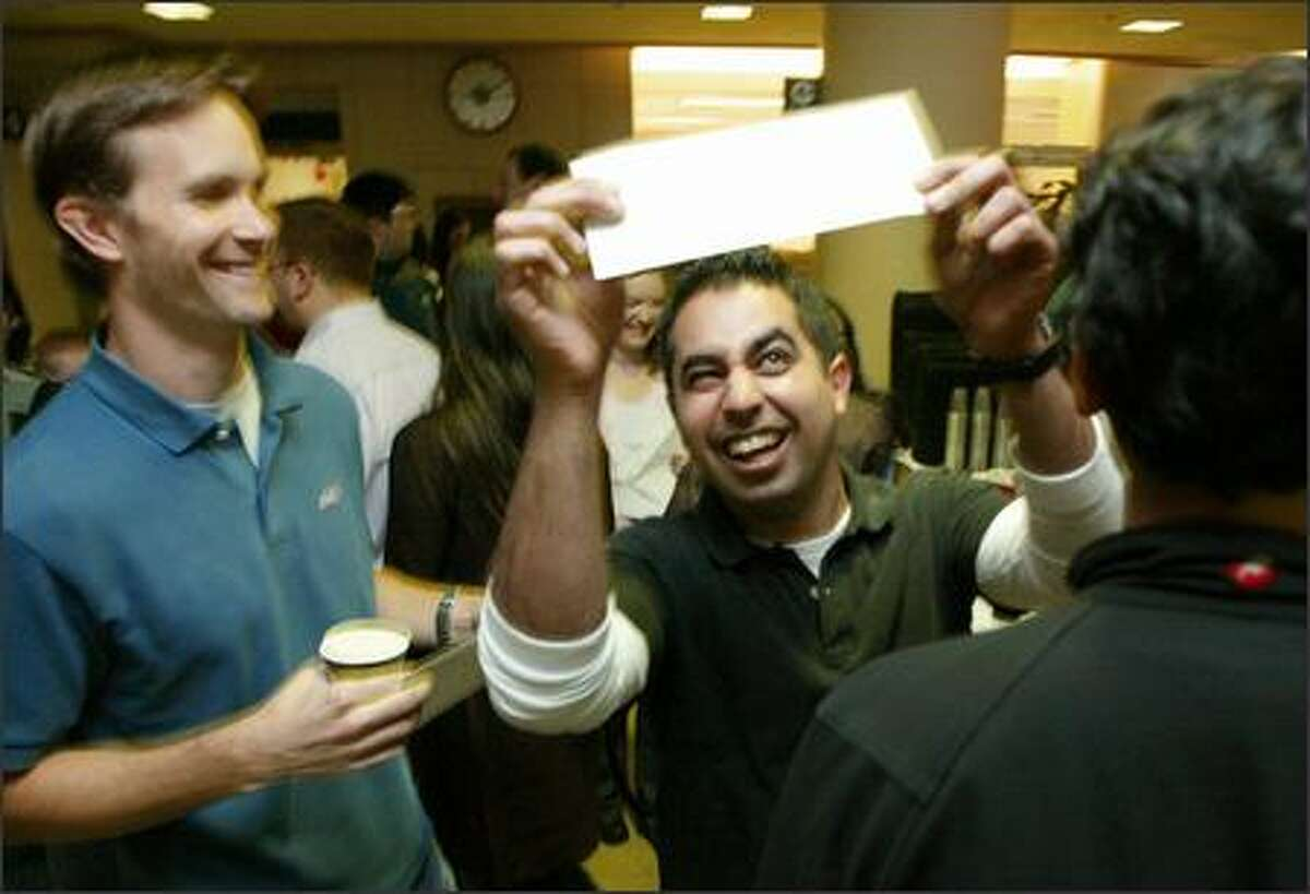 """Adi Dabestani, 30, eyes the envelope that he said was holding his destiny -- the medical residency program he was """"matched"""" with after finishing at the University of Washington medical school. Dabestani, who grew up in Marysville, was matched with the UW Medical Center, one of his top choices. At left is Erik Brand, one of Dabestani's roommates who had also just received an envelope containing his match."""