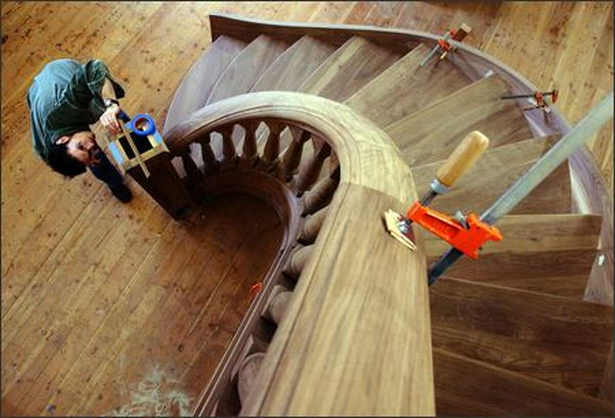 """Paul Savino, lead designer and craftsman at Seattle Stair and Design, works on finishing the starter newel post on the """"Carter"""" spiral staircase at the company workshop. The custom hand-built, 14-foot-high staircase is made from Black Walnut, weighs over a ton and has taken almost nine months to complete. When finished it will be installed in a Friday Harbor home."""