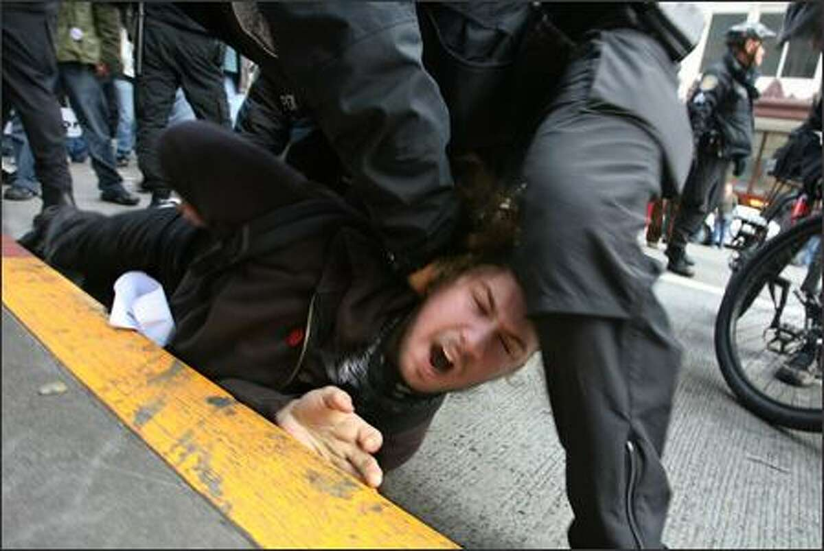 Seattle Police officers wrestle an anti-war protester to the ground. The momentary scuffle ended with the arrest of a 22-year-old Tacoma activist. The man was arrested for allegedly assaulting two counter-protesters, Seattle Police spokesman Sean Whitcomb said. No one was hurt. The man was participating in an anti-war protest to mark the fourth anniversary of the Iraq war. The protest starting at Westlake Center and progressed through the downtown area on Sunday in Seattle