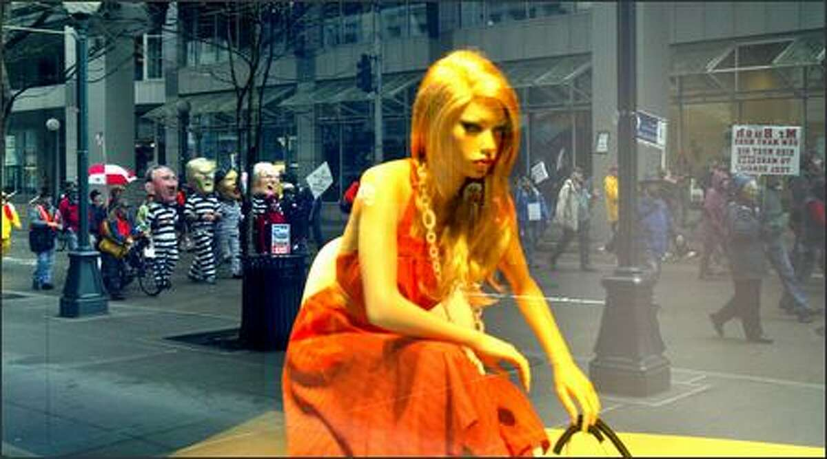 A mannequin in a Nordstrom display window looks over anti-war protesters marching down 5th Avenue in Seattle on Monday. Hundreds turned out for the event opposing the war in Iraq.