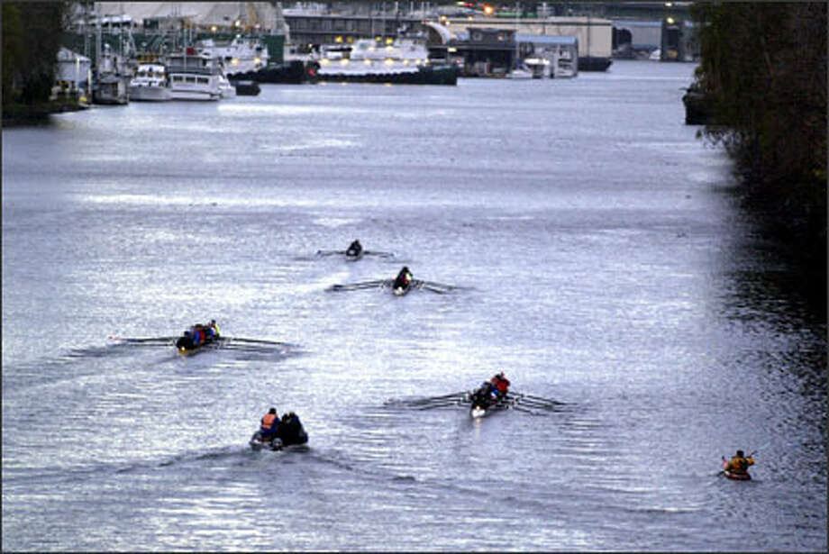 Members of Seattle's rowing community pay tribute to Seattle police Officer Jack Lone by paddling toward Third Avenue Northwest and Northwest 36th Street on the Lake Washington Ship Canal, where Lone died Wednesday while trying to help secure an old tugboat. Lone, 39, had worked in the harbor unit for five years. Photo: Jim Bryant, Seattle Post-Intelligencer / Seattle Post-Intelligencer