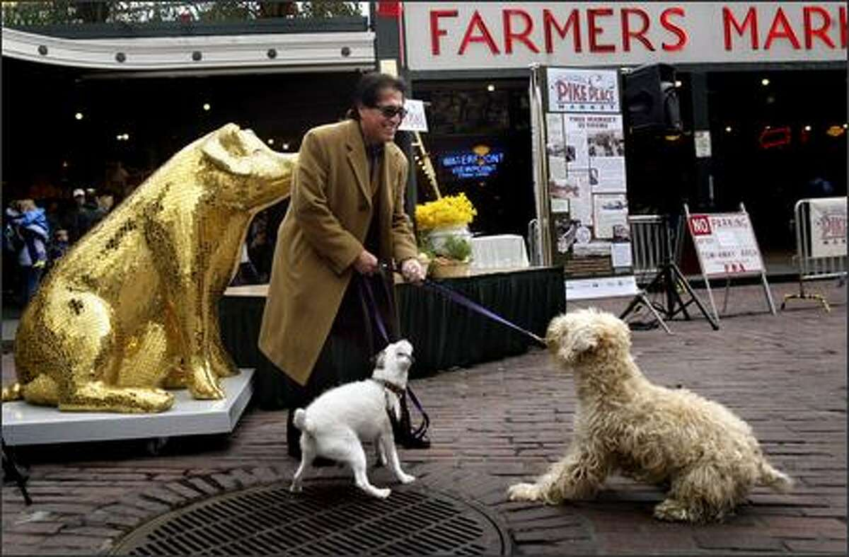 Gil Trujillo tries to convince Norton, left, and Chumley to pose for a picture with him in front of Lucky, a pig decorated by artist Rebecca DeVere for Washington Mutual, in front of Pike Place Market Tuesday. Lucky was on hand to help kick off of the Centennial Celebration of the Pike Place Market, which featured speeches by market and city officials, a musical performance, dancing fish and free cake for the public.