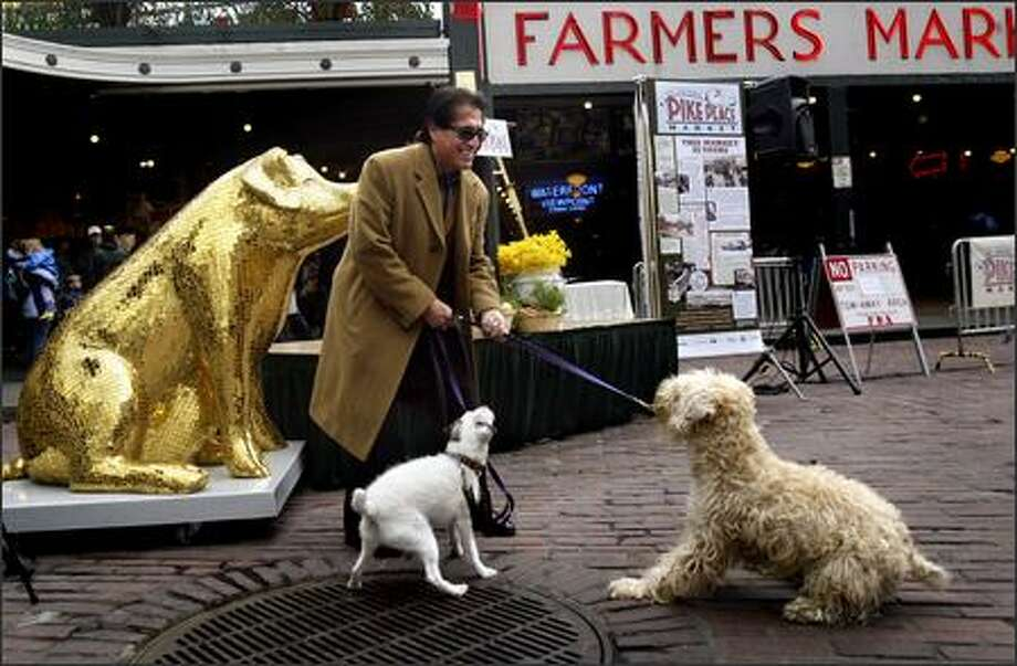 Gil Trujillo tries to convince Norton, left, and Chumley to pose for a picture with him in front of Lucky, a pig decorated by artist Rebecca DeVere for Washington Mutual, in front of Pike Place Market Tuesday. Lucky was on hand to help kick off of the Centennial Celebration of the Pike Place Market, which featured speeches by market and city officials, a musical performance, dancing fish and free cake for the public. Photo: Andy Rogers, Seattle Post-Intelligencer / Seattle Post-Intelligencer