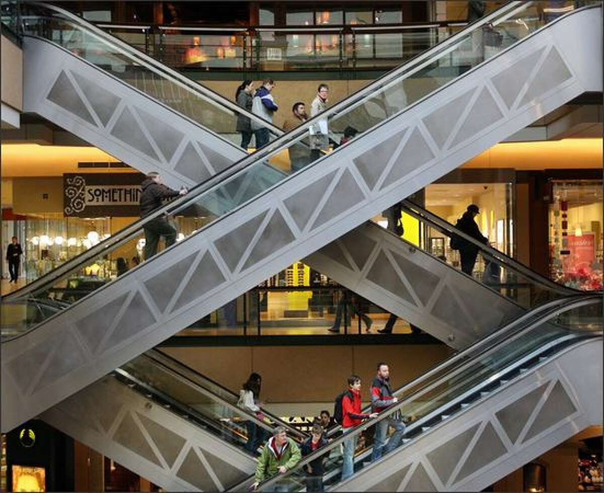 Shoppers and diners ride the escalators at Pacific Place shopping center in downtown Seattle.