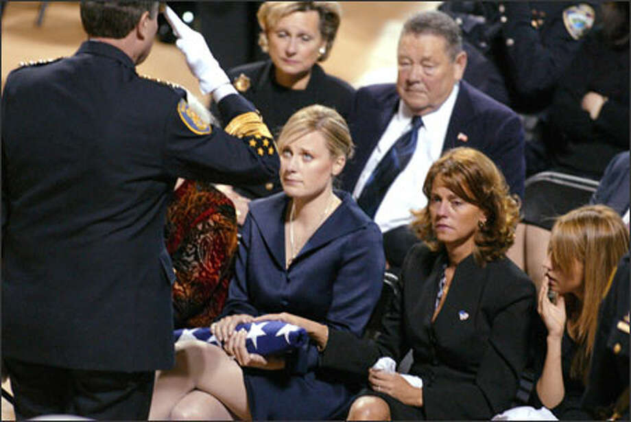 Seattle police Chief Gil Kerlikowske salutes Officer Jackson Lone's wife, Jeannie, after she was presented with a flag at a memorial service for her husband. Photo: Gilbert W. Arias, Seattle Post-Intelligencer / SEATTLE POST- INTELLIGENCER