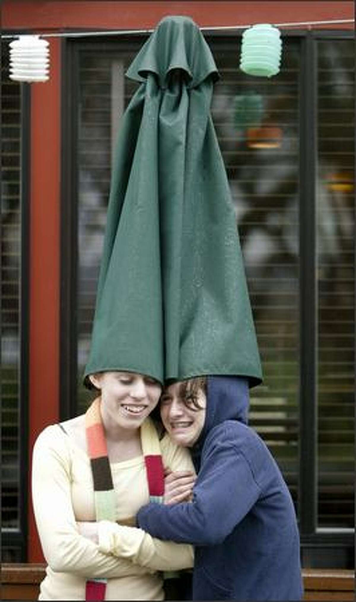 Alea Christiansen, left, and Kate Baron, both eighth-graders at Billings Middle School, get a little creative as they use a patio umbrella to try to keep dry while waiting to enter the Green Lake Bar & Grill in Seattle on Wednesday. The school, in a partnership with the restaurant, exchanges weekly hot meals for students for parking space for the restaurant's patrons. Today, that rain will be back.