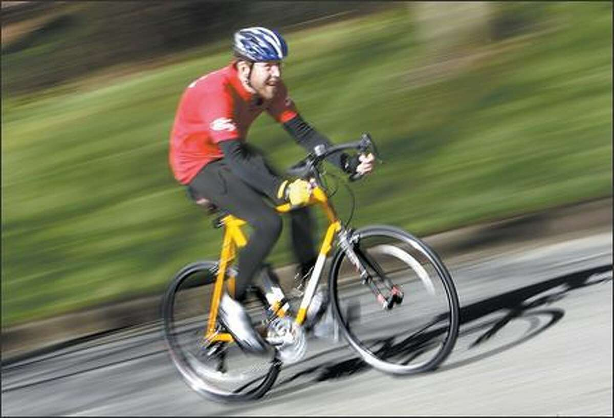 Aaron Barrett rides a custom-made bike after chemotherapy to treat pancreatic cancer caused calcium and bone loss that gives him a slight hunch. He is training for the Seattle to Portland Bicycle Classic.