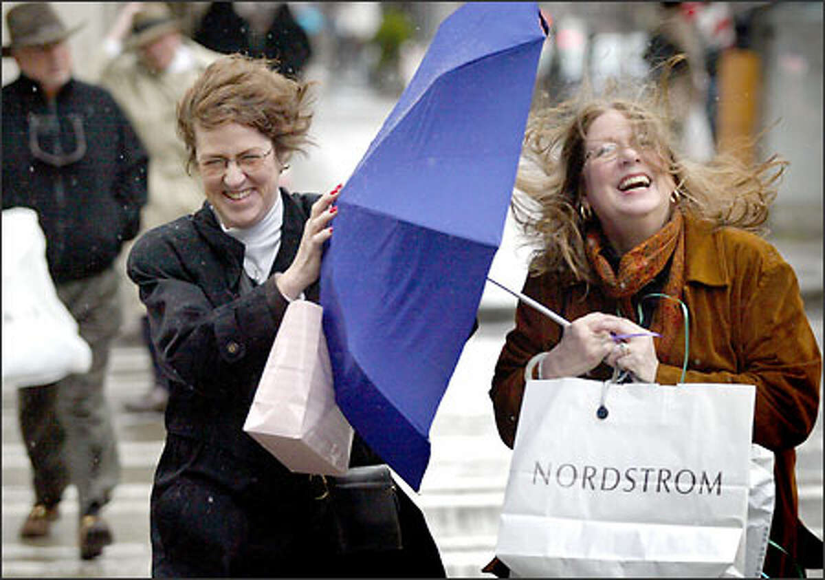 Windswept Katie Groth from Maryland and Helen Bowden-White from New York City, both visiting Seattle, grin and bear it as they battle to control their umbrella while crossing Union Street at Fourth Avenue. Umbrella users had to contend not only with rain but with high winds funneled between downtown buildings.