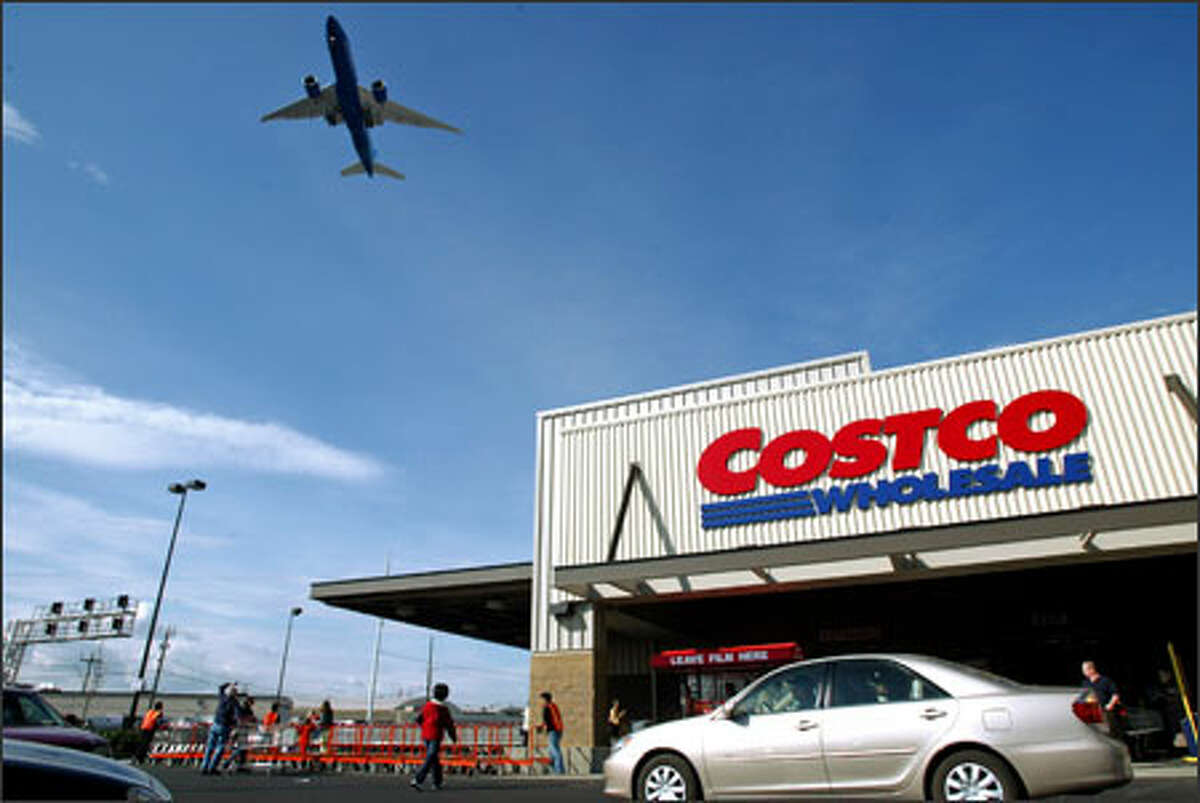 A jet soars overhead on opening day at Costco Wholesale Corp.'s new South Seattle store. The new faux warehouse replaces the company's very first store, built in an actual renovated warehouse.