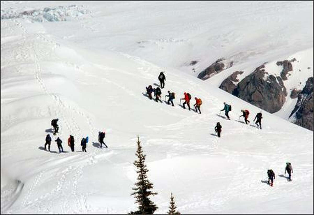A Mountaineers Club party practices climbing techniques on the slopes above Paradise. Spring is a fickle time of year at Rainier, and more snow is sure to fall. On average, Paradise gets 680 inches of the white stuff a year.