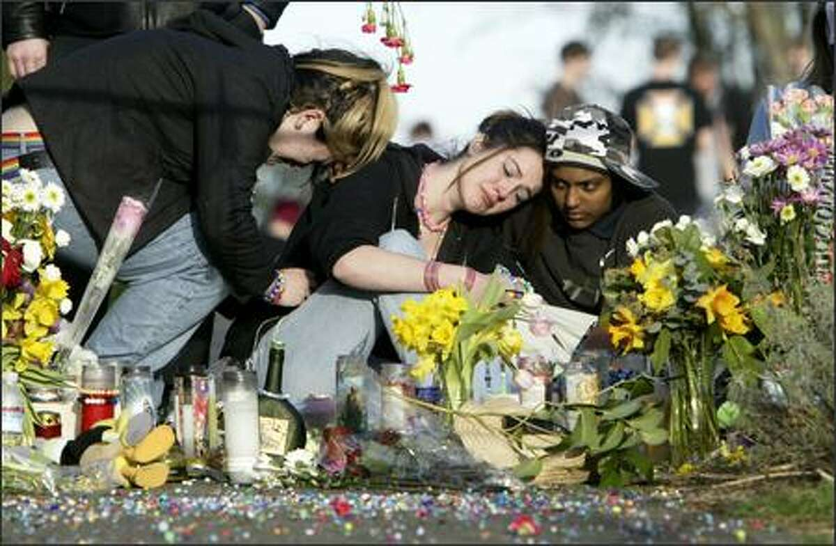 Friends of shooting victims comfort each other Monday at the scene of Saturday's rampage on East Republican Street. The woman at left declined to give her name, the woman in the middle gave her rave name, Tricse, and the man at right identified himself as Kneil.