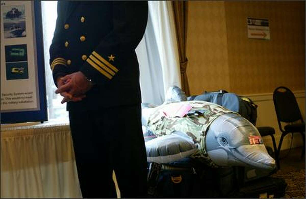 U.S. Navy Commander Jon Wood of the Naval Special Clearance Team 1 waits for a visitor to his booth during a presentation on the use of marine mammals as part of the Swimmer Interdiction Security System on Wednesday at the Holiday Inn in Seattle. In the background is an inflatable dolphin dressed in a T-shirt, part of a presentation by the protest group Knitting for Dolphins that says Puget Sound waters are too cold for the animals to live comfortably. The Navy plans to bring dolphins and sea lions to Naval Base Kitsap-Bangor as part of a security program.