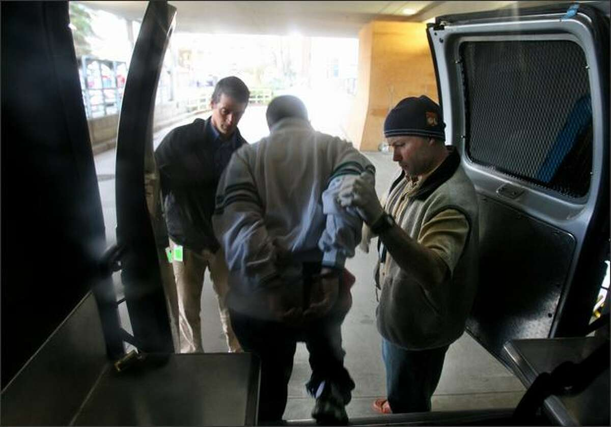 DOC community corrections officers Randy Vanzandt (left) and Thomas McJilton, deliver a mentally ill offender to Harborview Medical Center after she claimed she swallowed rocks of crack cocaine in Seattle. The offender was arrested for not checking in with her supervisors as required.