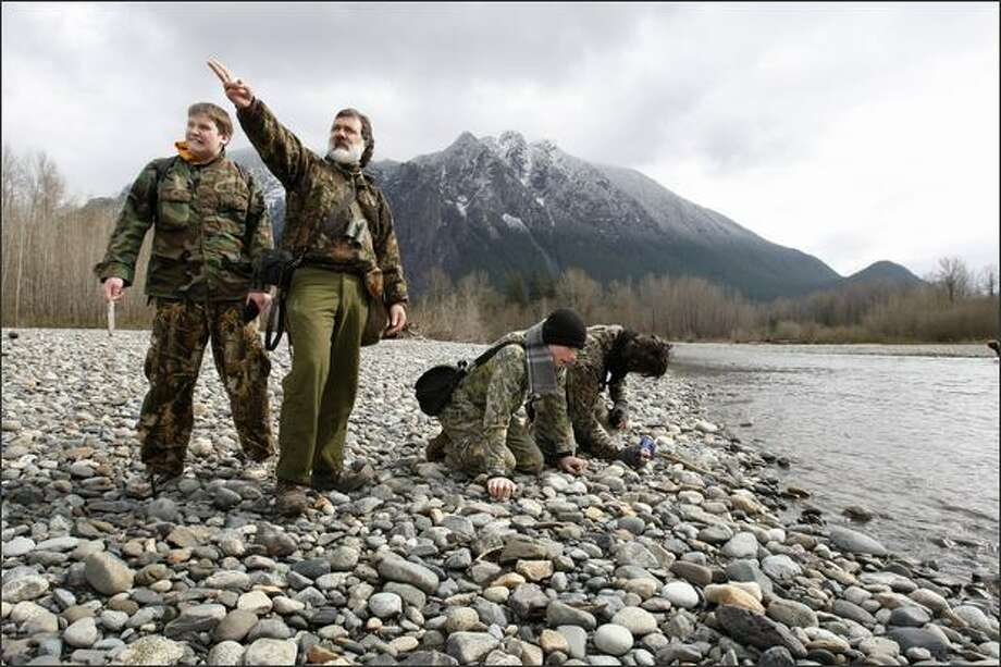 """Allan """"Hawkeye"""" Sande, pointing, director of the Quiet Heart Wilderness School, gives instruction beside the Snoqualmie River on tracking elk at the Three Forks Natural Recreation Area in North Bend. Far left is student Dylan """"Owl Hunter"""" Ruef, 16, of Bothell. In the background is Mt. Si. Photo: Meryl Schenker, Seattle Post-Intelligencer / Seattle Post-Intelligencer"""
