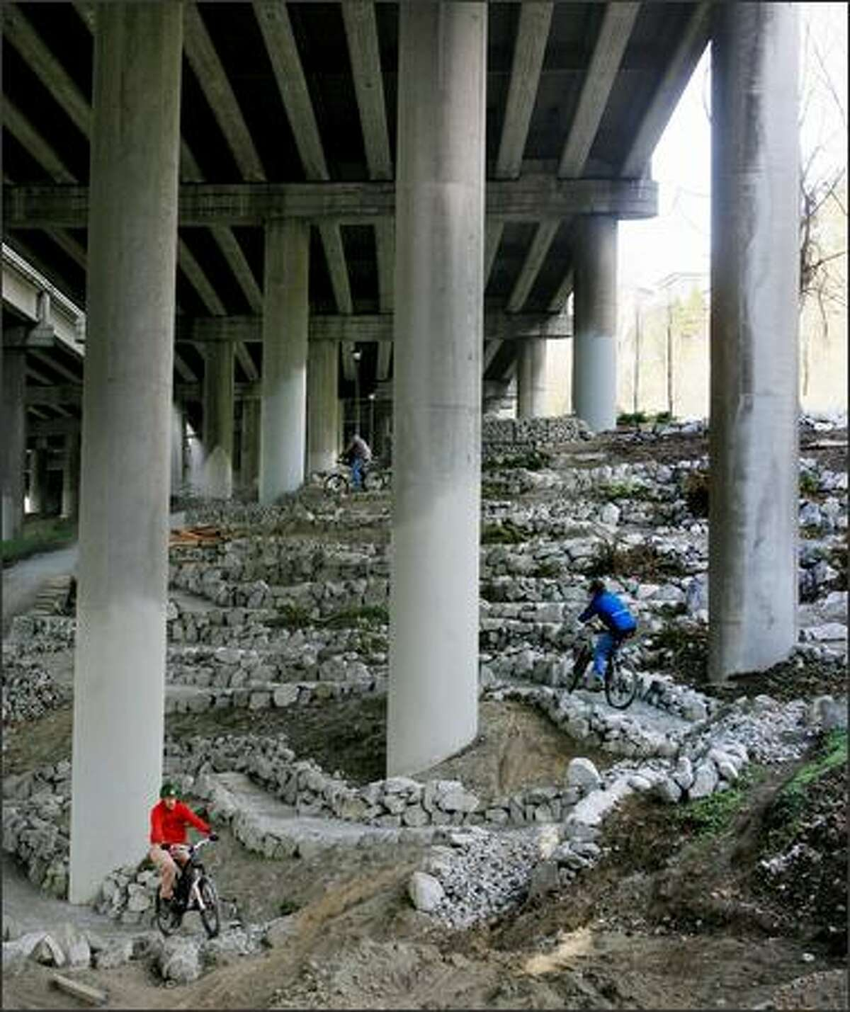 After a volunteer work party, members of the Backcountry Bicycle Trails Club ride the trail system they're constructing in Colonnade Park under Interstate 5 in Seattle's Eastlake neighborhood.