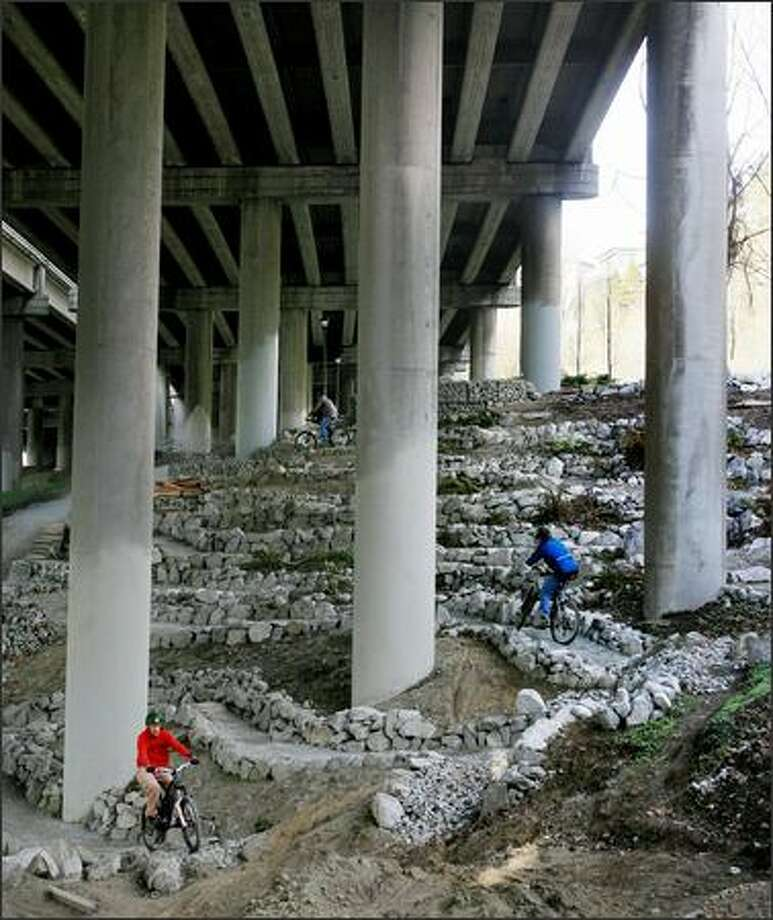 After a volunteer work party, members of the Backcountry Bicycle Trails Club ride the trail system they're constructing in Colonnade Park under Interstate 5 in Seattle's Eastlake neighborhood. Photo: Dan DeLong, Seattle Post-Intelligencer / Seattle Post-Intelligencer