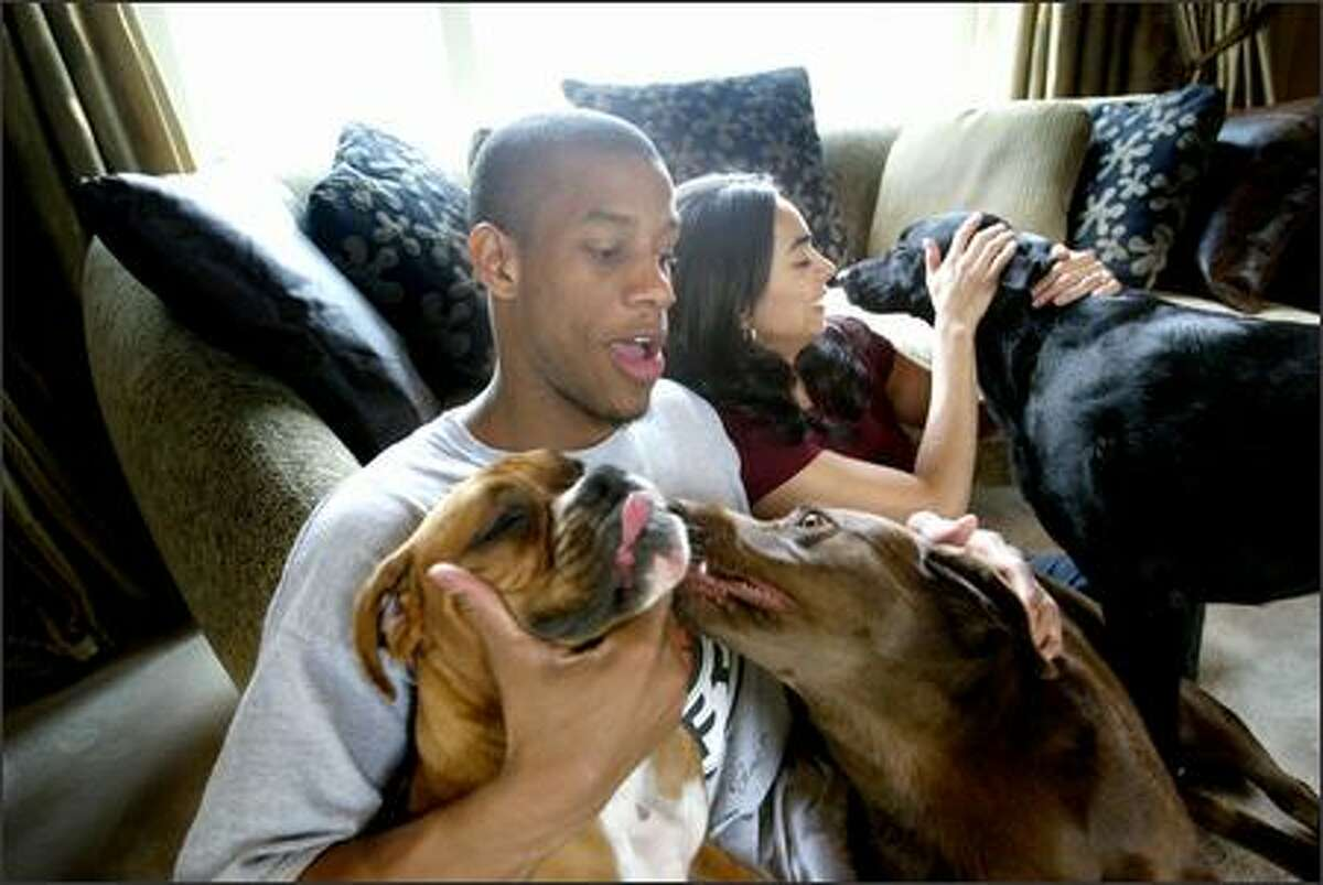 Sonics guard Antonio Daniels frolics with Tasha, a boxer, and Kuska, a chocolate lab, while fiancee Sonia Fuentes pets Sable, a black lab.