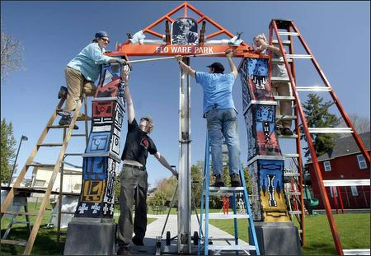 Artists, from left, Lauren Grossman, Fred Metz, Mark Fessler and Mark Rudis erect the