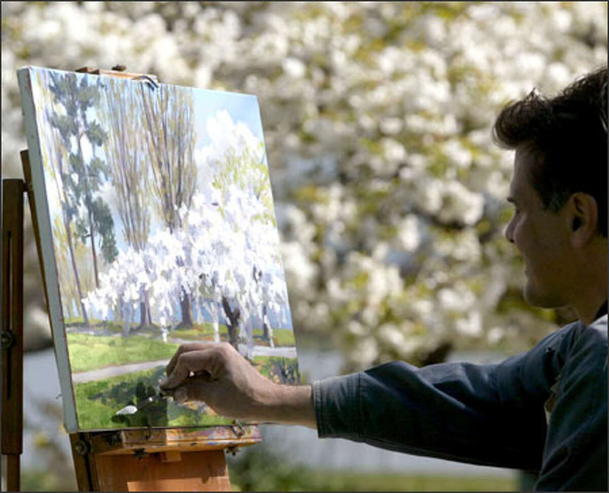 Taking advantage of a recent dry period in the weather, artist James Prouty uses his canvas to capture the blossoms in bloom around Green Lake in Seattle.