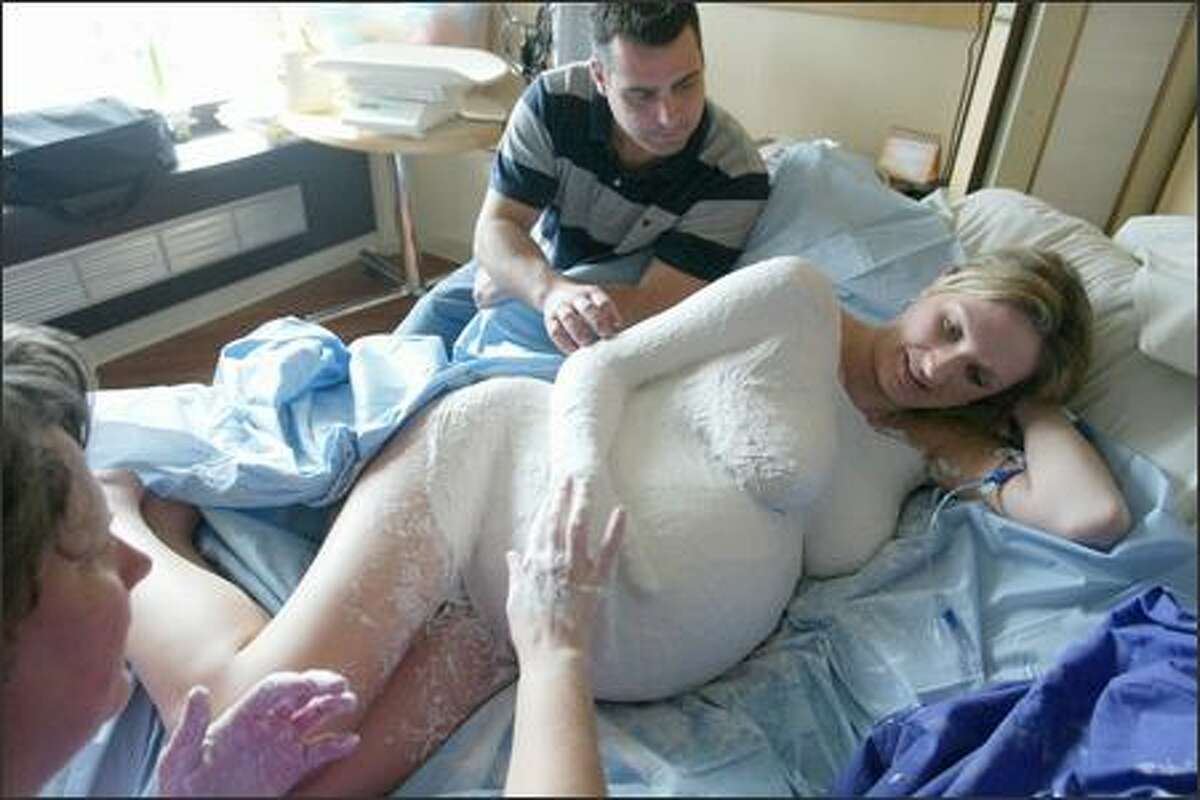Expectant mom of quintuplets Courtnee Stevenson had a belly mask -- a plaster of Paris cast -- of her belly made by Kim Radtke, at left. Her husband, Mike Stevenson, is at center. On Thursday, March 30, Courtnee gave birth to Aniston, Weston, Belle, Camilee and Scarlett.