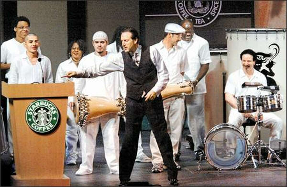 Howard Schultz, chairman and chief global strategist for Starbucks, lays down a baton after he directed the drum jam at the musically-oriented shareholders meeting in McCaw Hall yesterday.