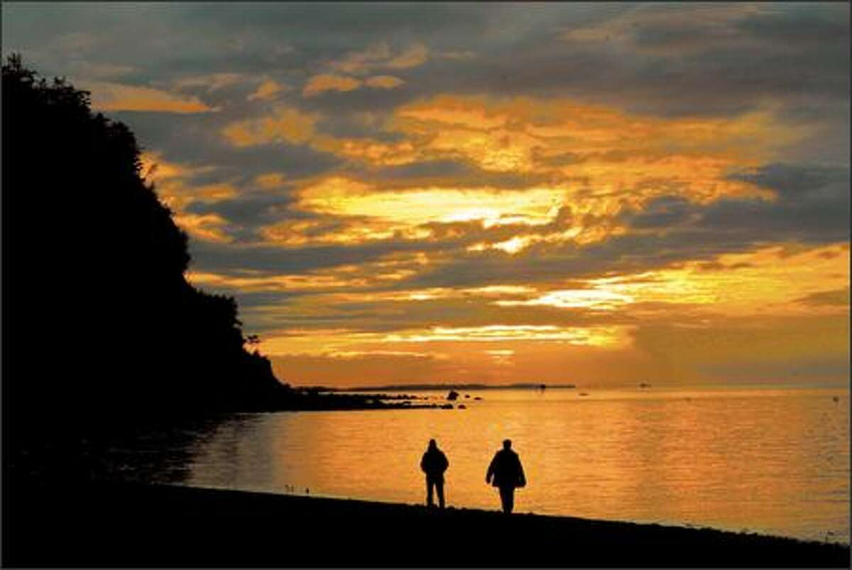 Nevada residents Giselle Tenhompel and Roger Farquhar take in a sunset along the edge of the Strait of Juan de Fuca at Fort Worden State Park.