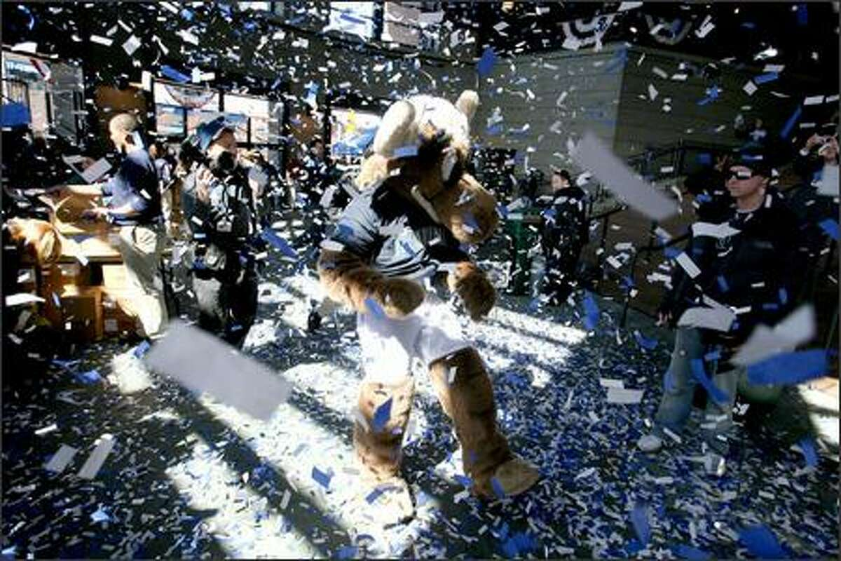 Mariners fans and the team mascot, the Mariner Moose, are showered with confetti as they enter Safeco Field to see the home team beat the Oakland A's 4-0 on opening day of the 2007 baseball season.