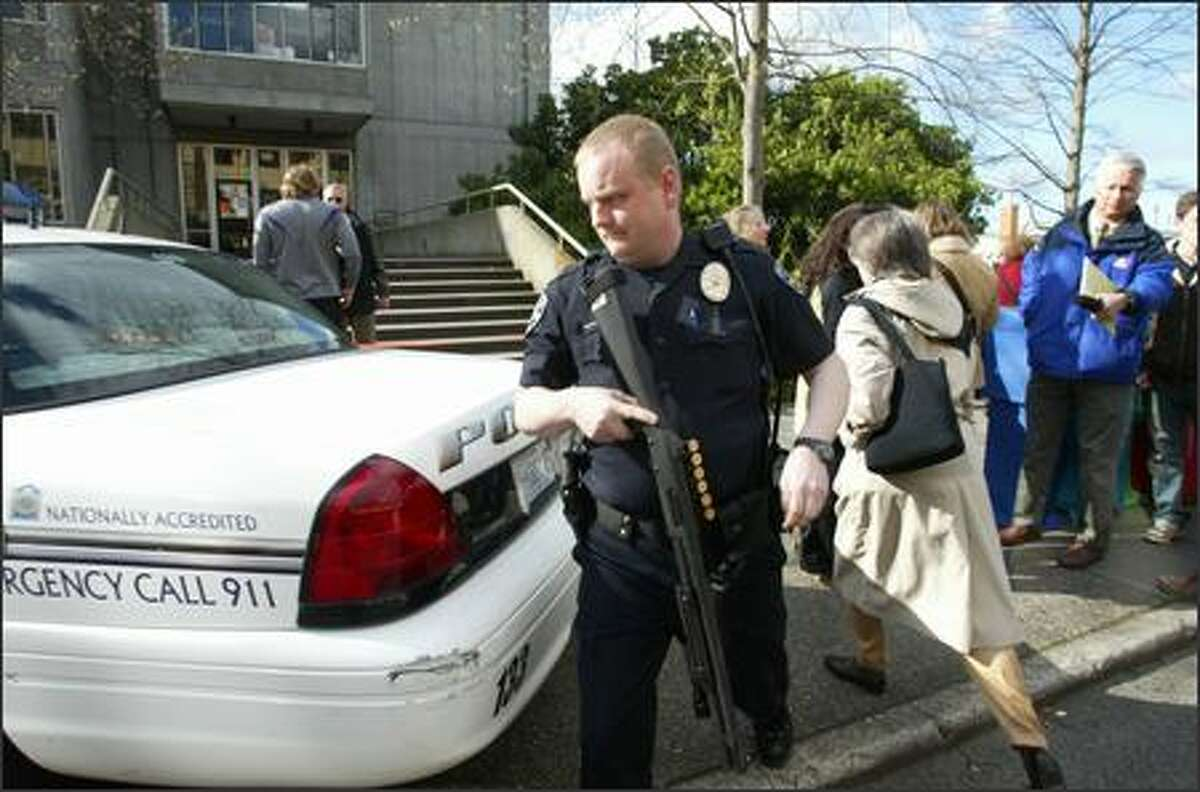 A campus police officer returns to his cruiser after police cleared Gould Hall at University of Washington following a shooting which resulted in two fatalities on Monday. Gould Hall houses UW's School of Architecture and Urban Planning.