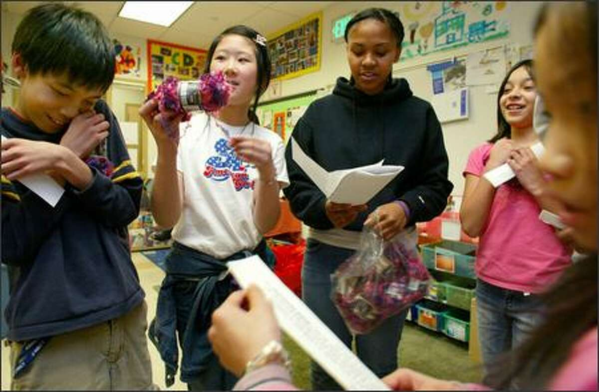 Garfield High School student Marita Phelps, center right, holds her notes as she leads a group of Maple Elementary School students in a role-playing exercise recently to teach them about how microloans help people in developing countries pull themselves out of poverty. The students, from left, Eddy Liu, Winnie Kwong, Vanessa Garcia and Khanh Phan exchange pretend money for pretend chickens. Phelps learned about microloans on a recent trip to Guatemala with Global Visionaries.