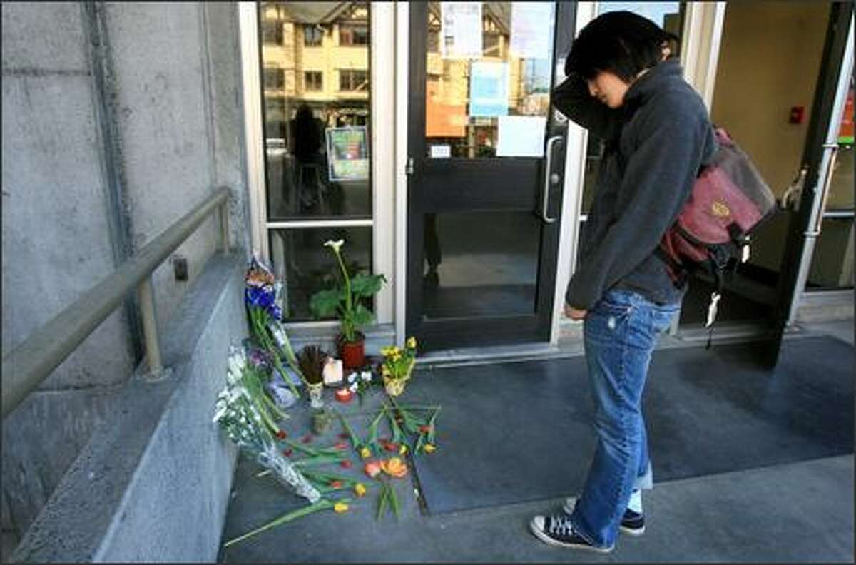 After placing flowers, Linda Pham, a UW landscape architecture student, pauses Tuesday at an impromptu memorial for Rebecca Griego outside the UW's Gould Hall. Griego was killed Monday by Jonathan Rowan, her ex-boyfriend, in her office in Gould Hall.