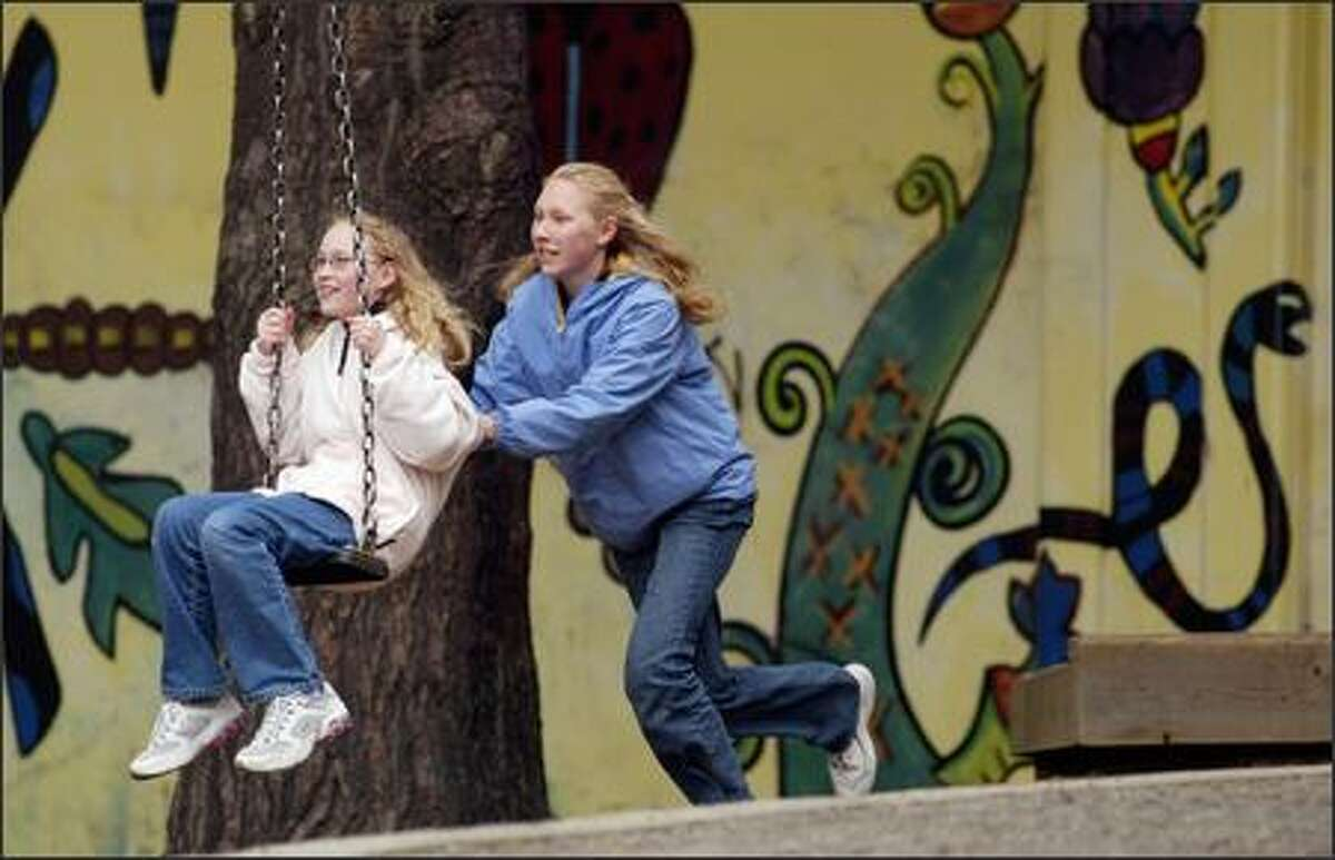 Taylor Fruth, 13, helps sister Haley, 10, add some momentum while using the zip line swing at Cowen Park on Wednesday. The Fruths, on spring break from Komomo, Ind., are here visiting relatives. They count the zip line, among other attractions such as Pike Place Market and Pacific Science Center, as worth revisiting since their last trip.