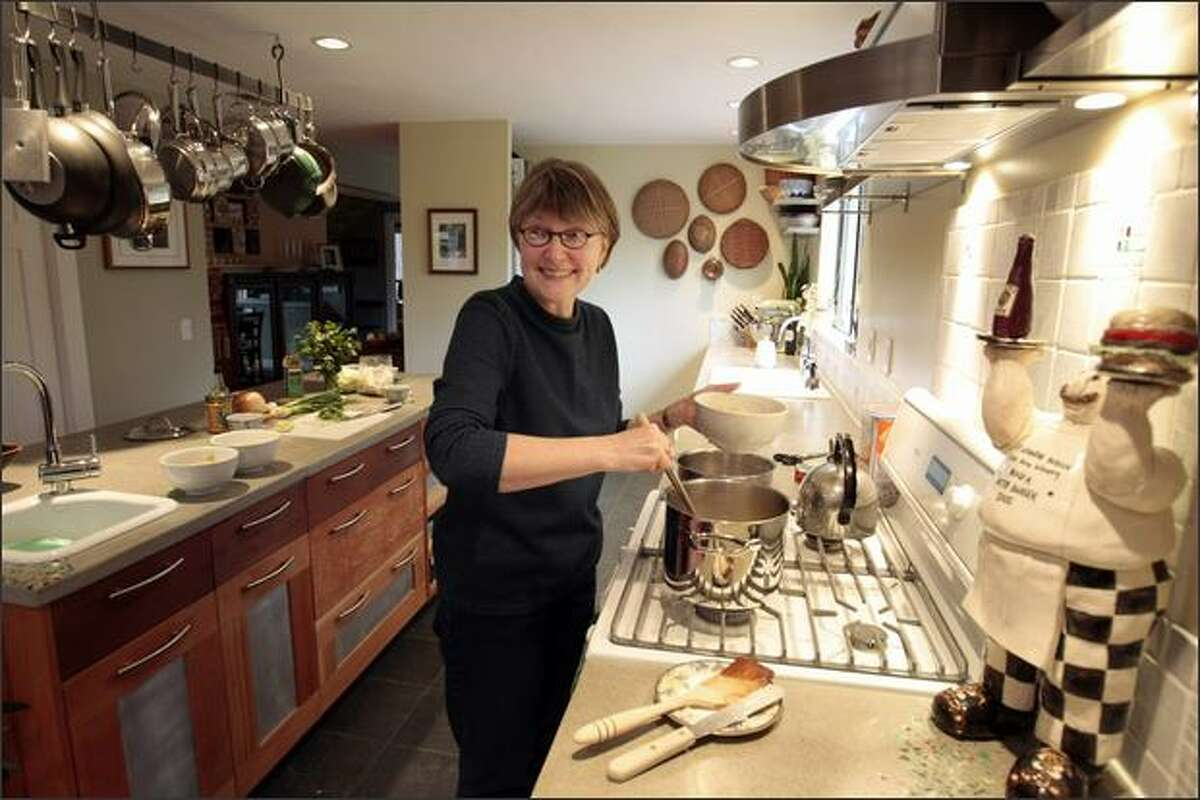 Ellie Mathews gives her husband Carl Youngmann a smile, while preparing lunch in their Port Townsend home. Mathews started with a Rachael Ray recipe (Chicken Satay Noodle Soup) and made modifications according to her taste. On the right is the award she won for her Vietnamese-style burger in 2005 along with $10,000. She named him